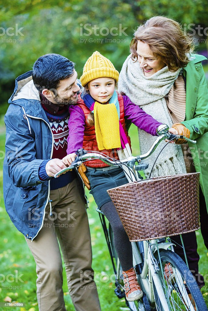 Father, daughter and grandmother in park stock photo