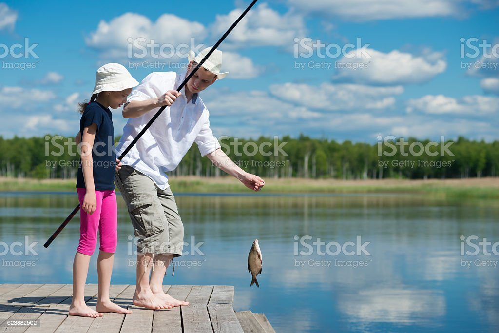 Father daughter caught a fish in the river stock photo