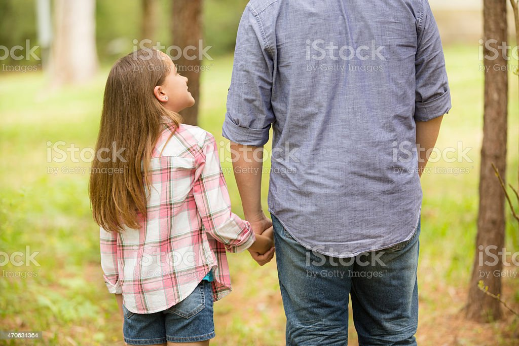 Father, daughter hold hands outdoors. Parent, child. Love, affection. stock photo