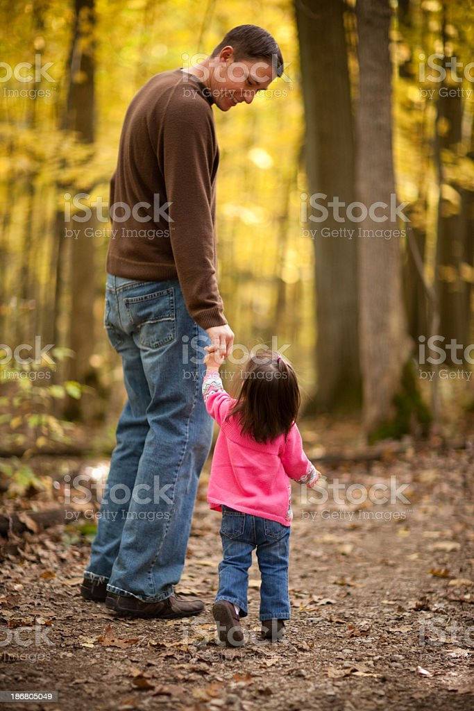 Father & Daughter Walking on Trail Through Autumn Woods royalty-free stock photo