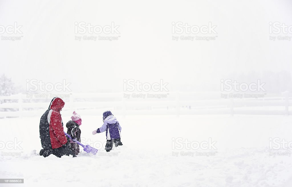 Father & Daughters Playing in Snow royalty-free stock photo