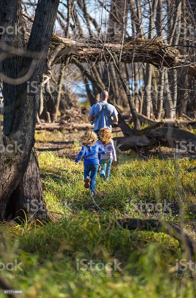Father & Daughters Walking Through Woods in Autumn stock photo