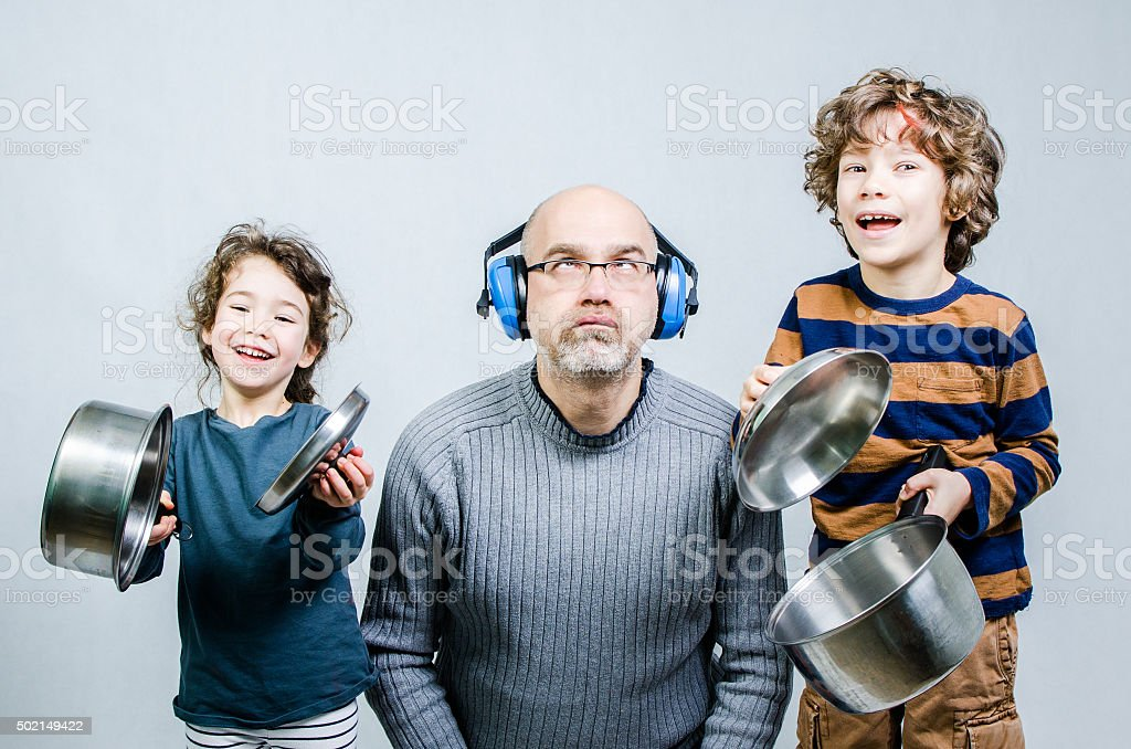 Father discouraged by kids making noise with cauldrons stock photo