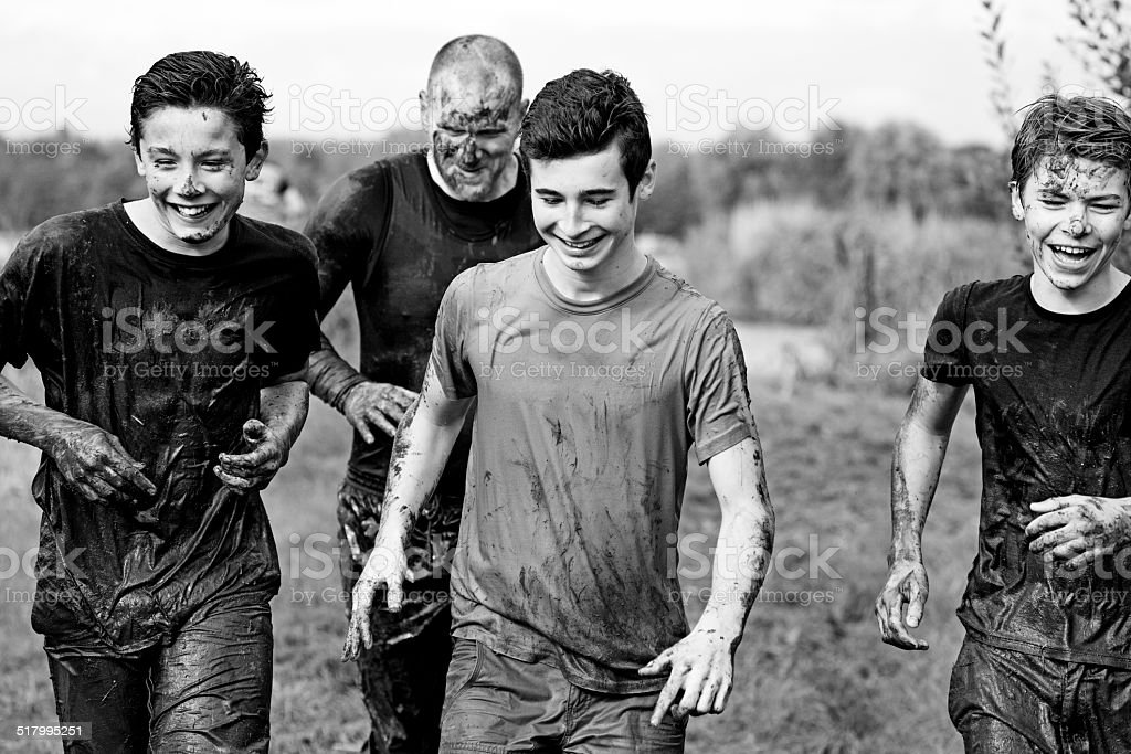 father doing mud run with his sons stock photo