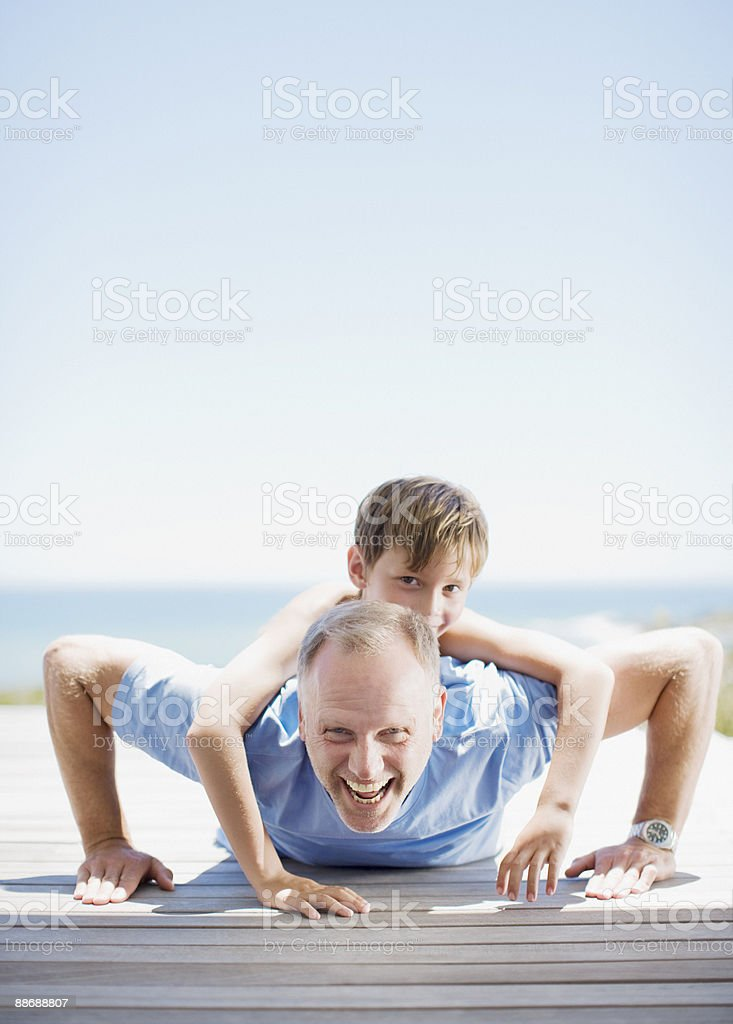 Father doing push-ups with son on his back stock photo