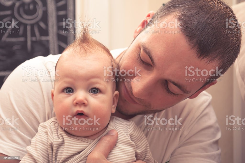 Father embracing his little baby. Father is looking on baby, baby is...
