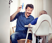 Father feeding baby in high chair