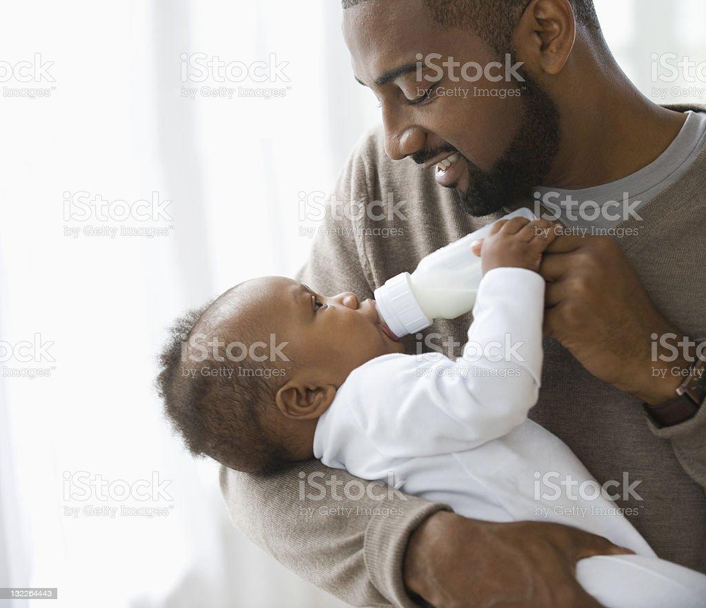 Father feeding son stock photo
