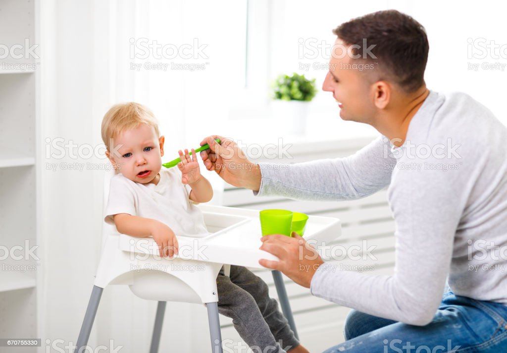 Father feeds the cry baby son stock photo