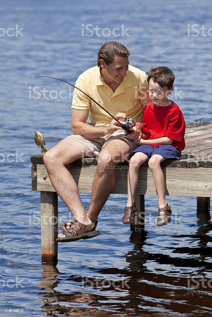 Father Fishing With His Son On A Jetty royalty-free stock photo