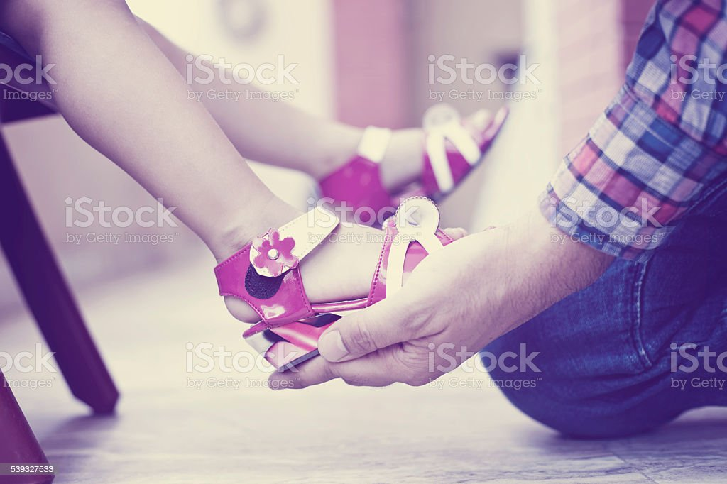 Father getting dressed to his daughter stock photo