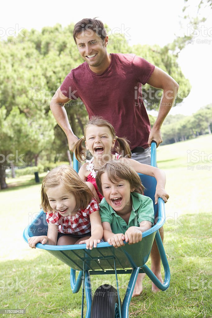 Father Giving Children Ride In Wheelbarrow stock photo