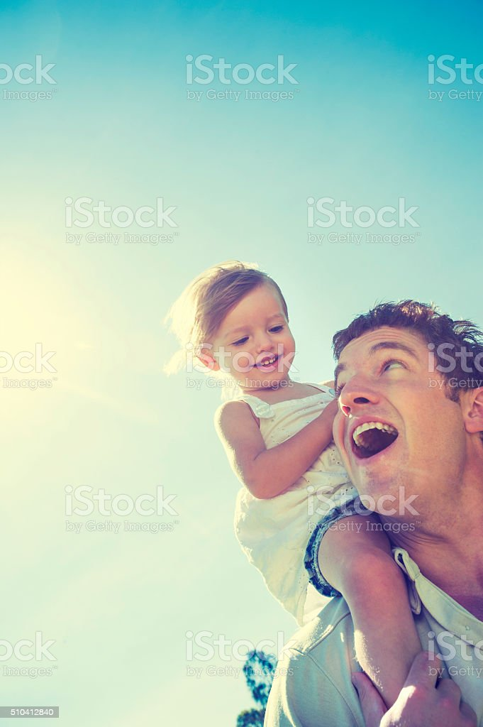 Father giving his daughter a piggy back ride. stock photo