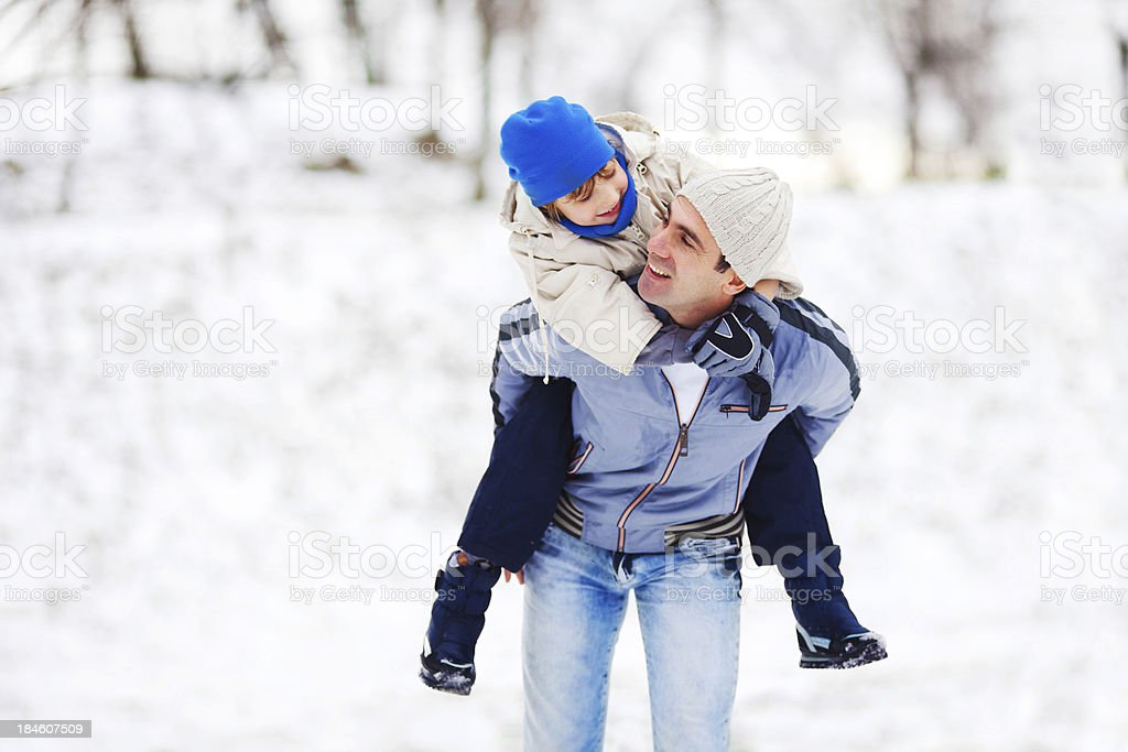 Father giving his son a piggyback ride royalty-free stock photo