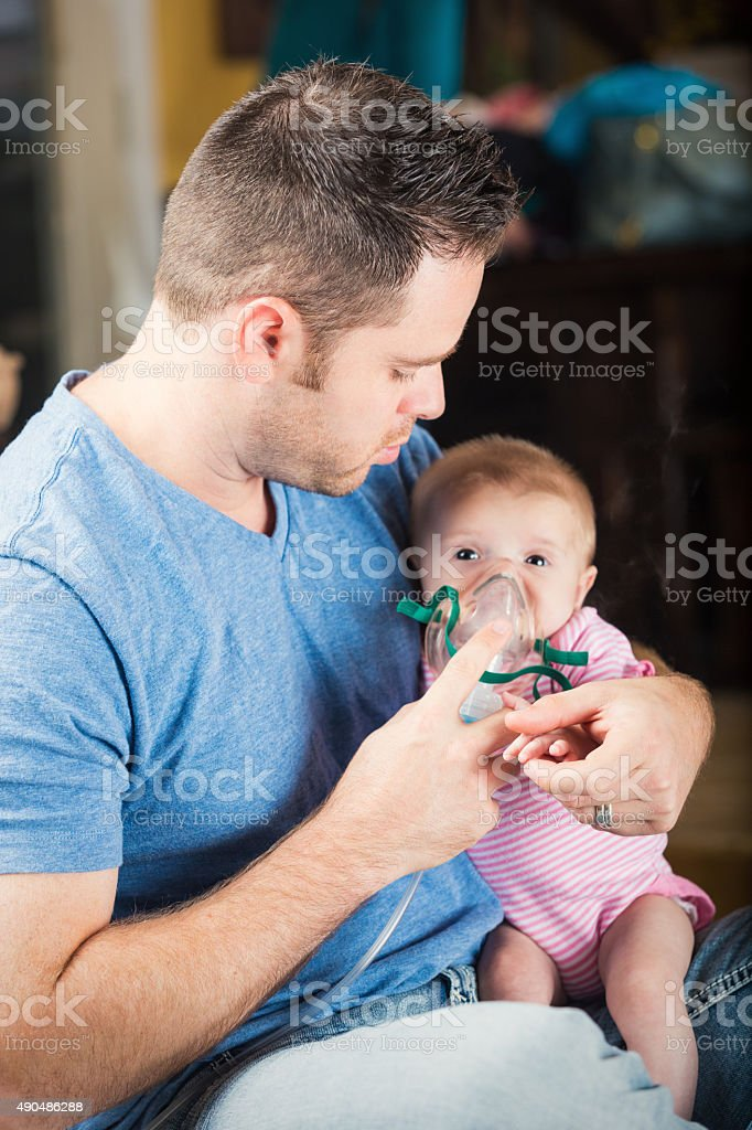 Father giving infant daughter breathing treatment for cystic fibrosis stock photo