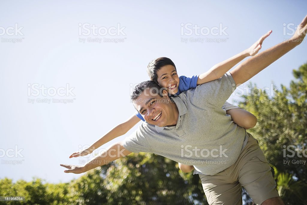 Father Giving Piggyback Ride To Son stock photo