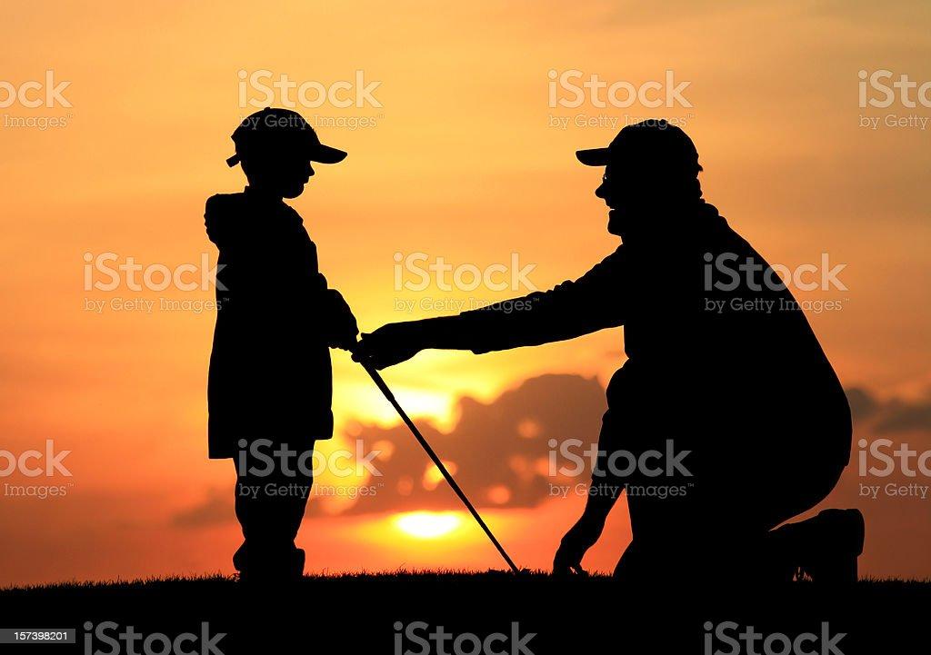 Father Giving Son Junior Golf Lesson stock photo