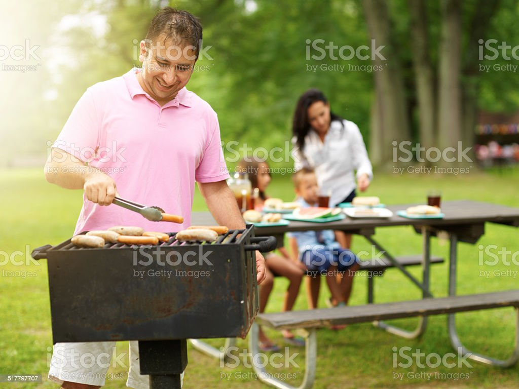 father grilling for family at park stock photo