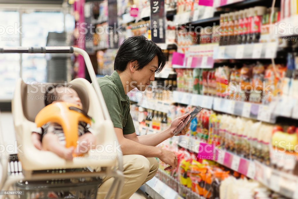 Father grocery shopping at the supermarket stock photo