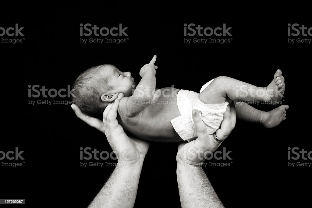 father hands infant son relationship stock photo
