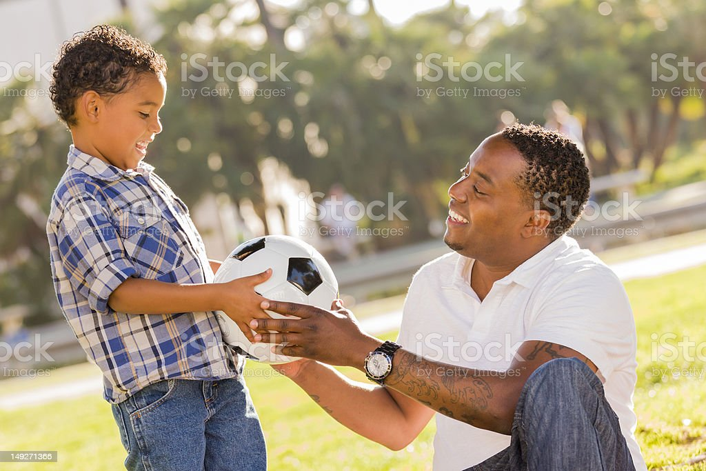 Father Hands New Soccer Ball to Mixed Race Son royalty-free stock photo
