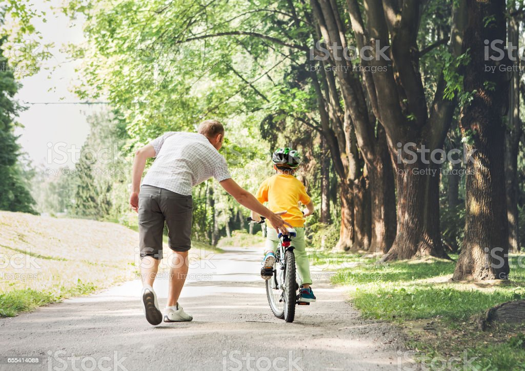 Father help his son ride a bicycle stock photo