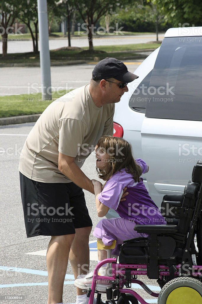 Father helping daughter out of wheelchair royalty-free stock photo