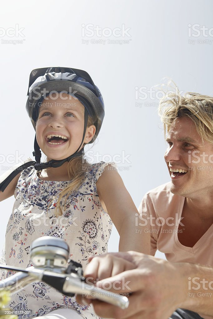 Father helping daughter (9-11) ride bicycle, low angle view royalty-free stock photo