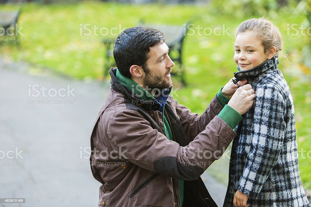 Father Helping Daughter With Coat stock photo