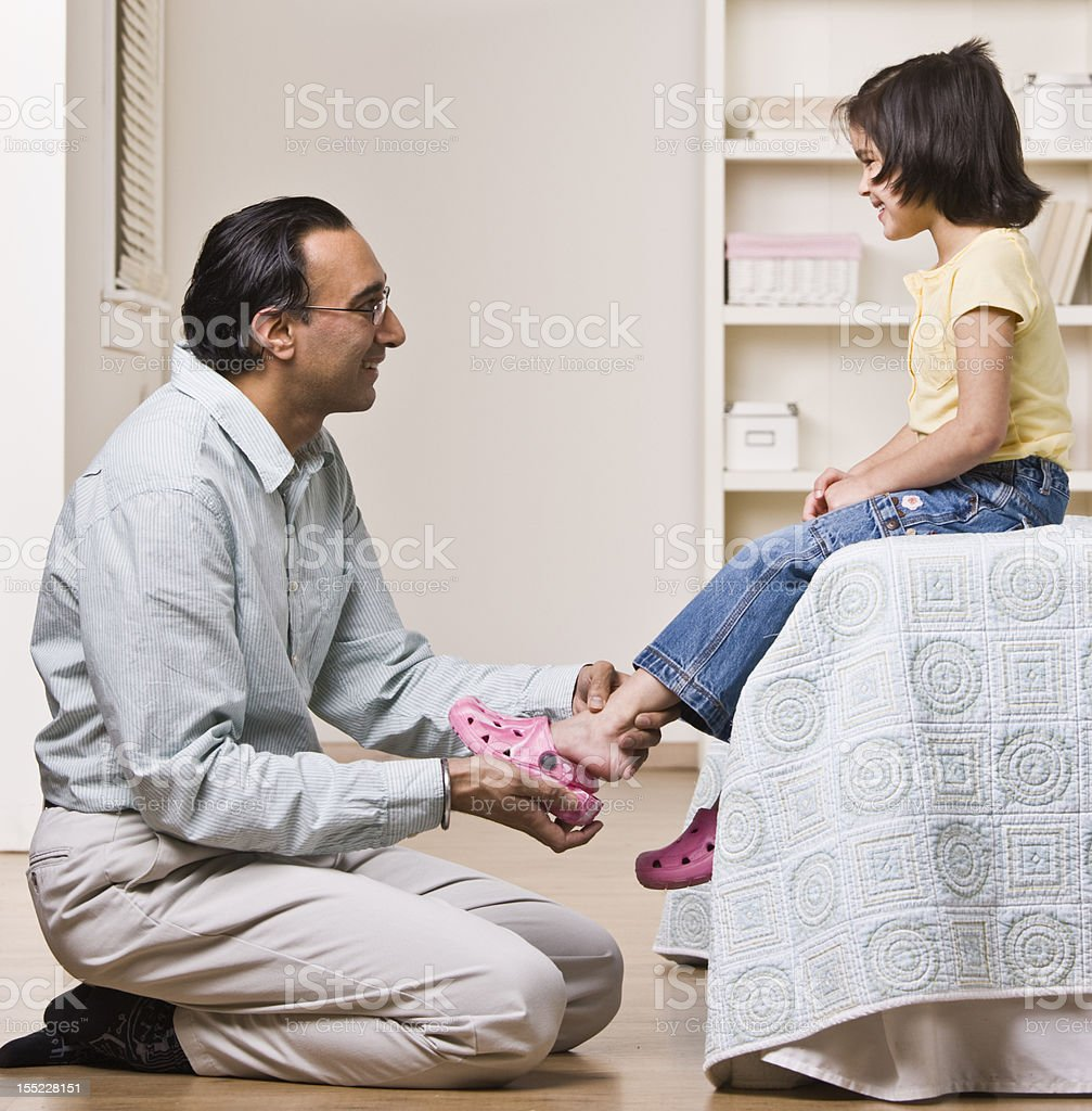 Father Helping Daughter with Shoes royalty-free stock photo