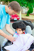 Father helping disabled son in wheelchair drink from straw cup