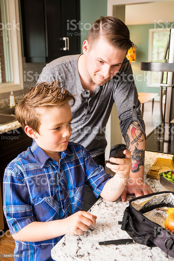 Father helping his diabetic son monitor his blood sugar. stock photo