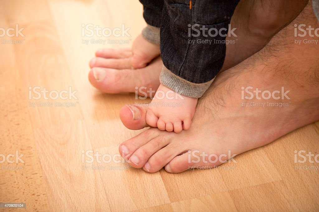 Father helping his son for the first steps stock photo