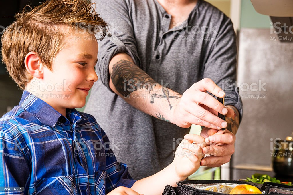 Father helping his son monitor his diabetes stock photo
