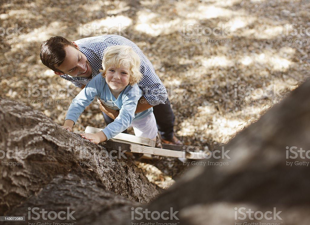 Father helping son climb tree outdoors royalty-free stock photo