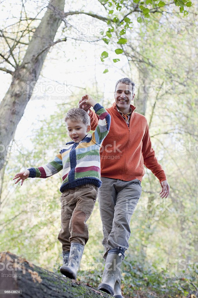 Father helping son cross log outdoors stock photo