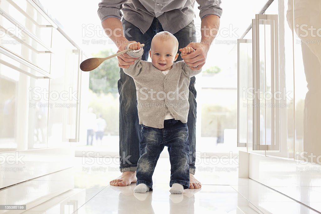 Father helping son learn to walk stock photo