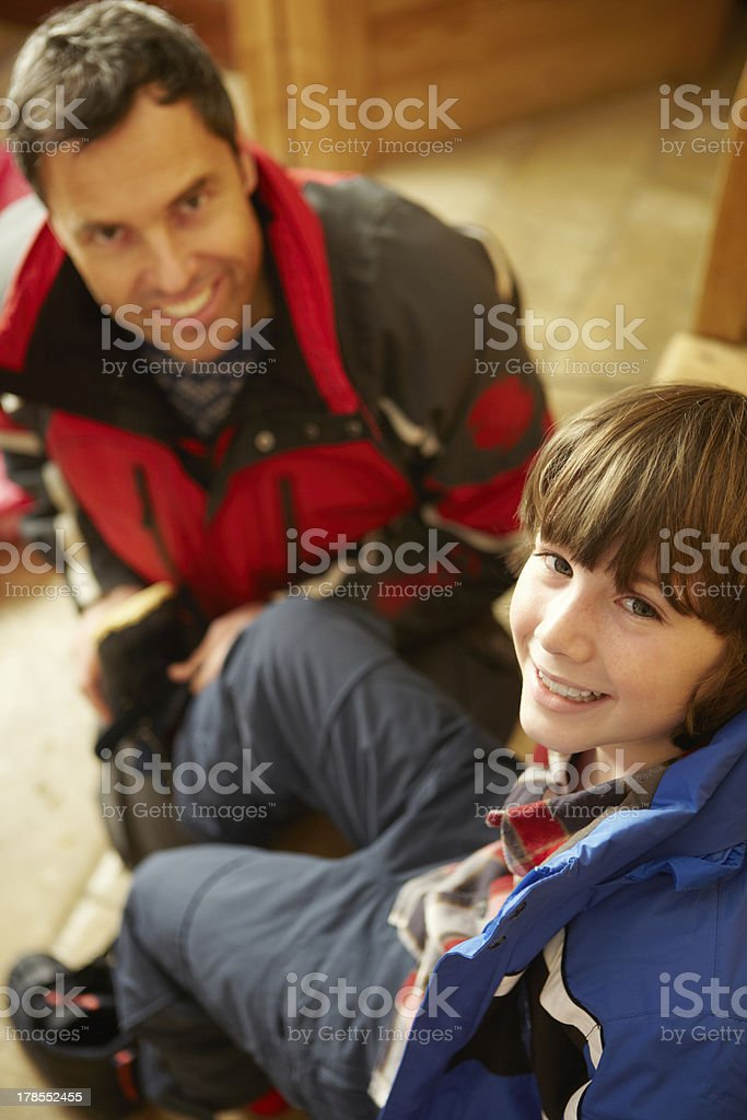 Father Helping Son To Put On Warm Outdoor Clothes royalty-free stock photo