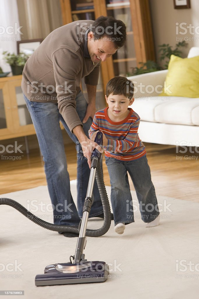 Father helping son to vacuum royalty-free stock photo