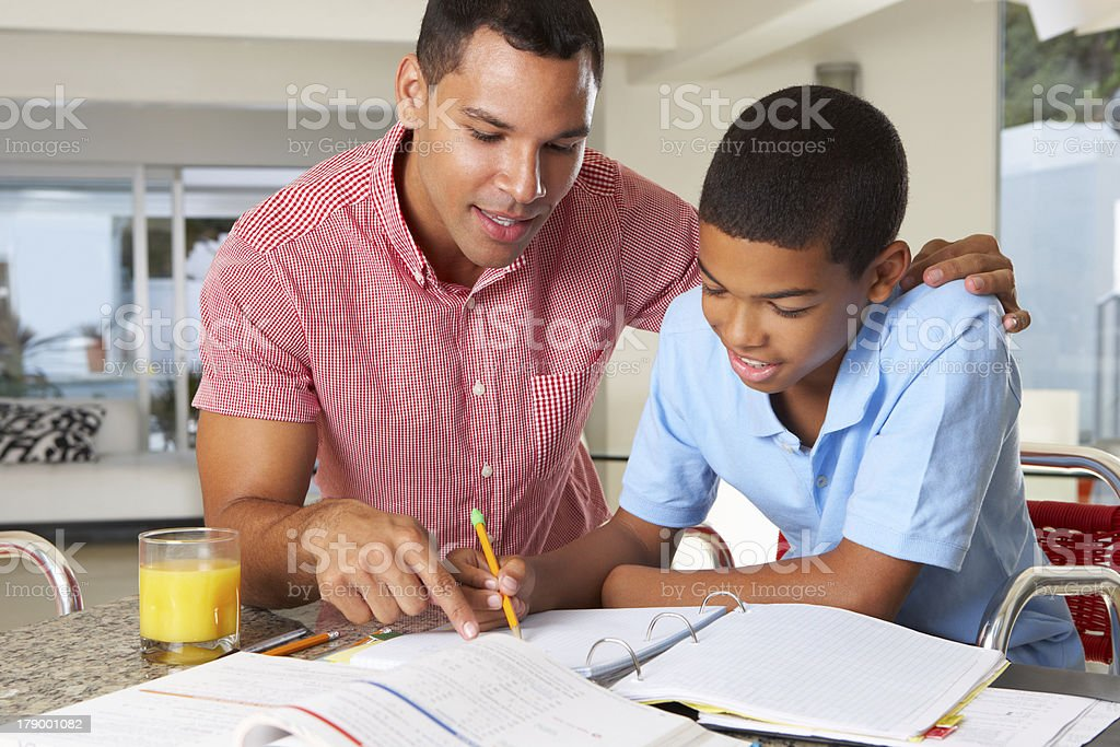 Father Helping Son With Homework In Kitchen stock photo