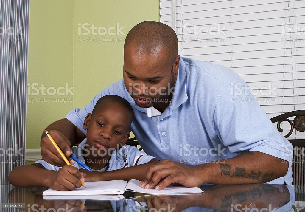 Father helping son with homework on a table royalty-free stock photo