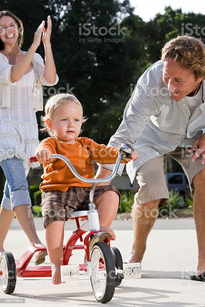 Father helping toddler ride tricycle, mother clapping royalty-free stock photo