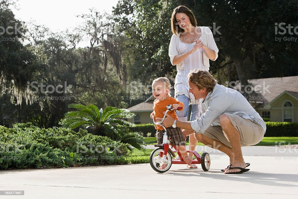 Father helping toddler ride tricycle, mother standing behind stock photo