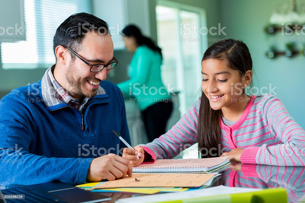 Father helps daughter with homeschool assignment stock photo