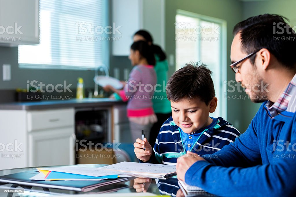 Father helps elementary age sone with homework stock photo