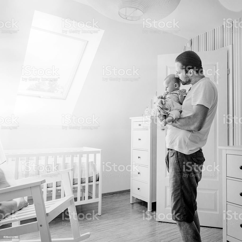 Father holding and cuddling little baby boy tenderly, baby's room stock photo