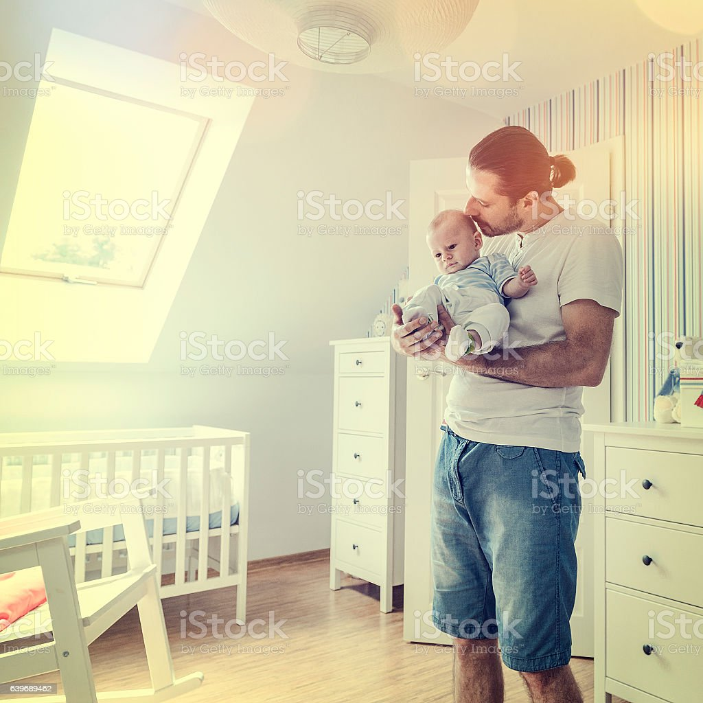 Father holding and hugging little baby boy tenderly, baby's room stock photo