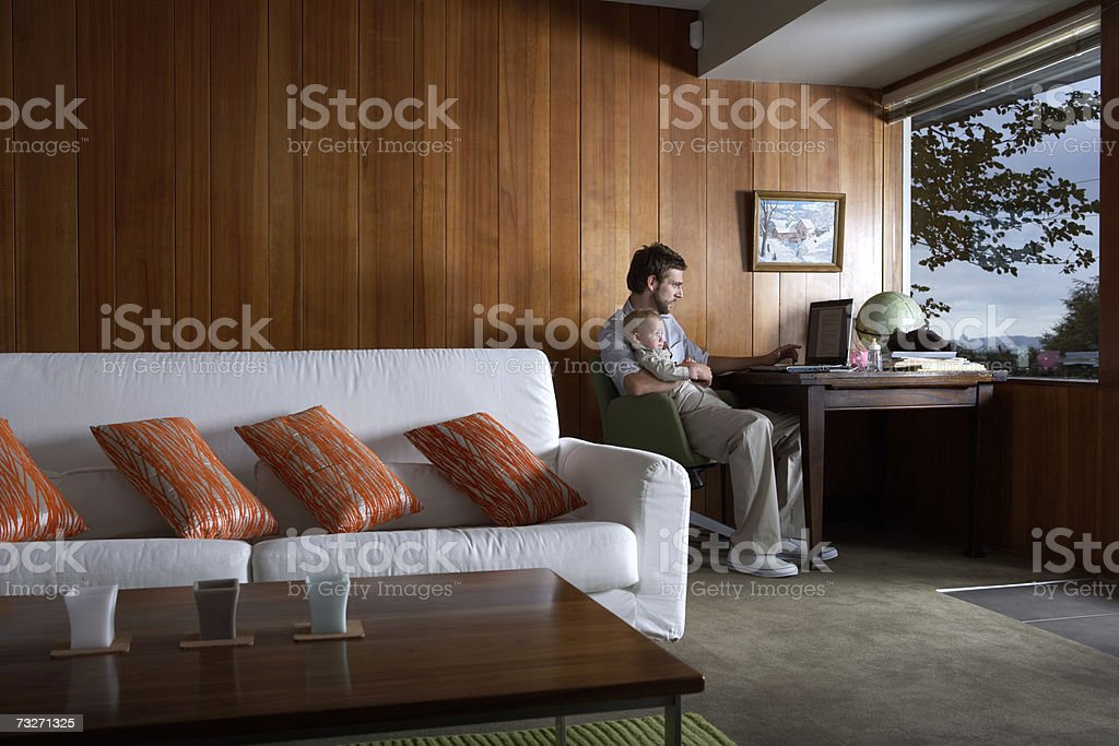 Father holding baby girl (6-9 months) at laptop in living room royalty-free stock photo
