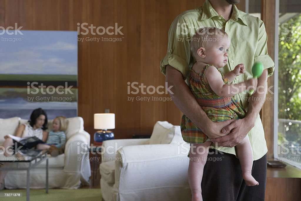 Father holding baby girl (9-12 months), with mother and sister (5-7) in background royalty-free stock photo