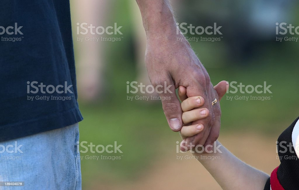 father holding child's hand royalty-free stock photo